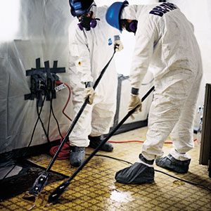 Workers scrape off floor tiles containing asbestos